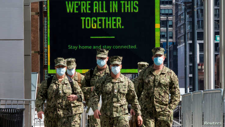 U.S. military personnel wearing face masks arrive at the Jacob K. Javits Convention Center, as the outbreak of the coronavirus…