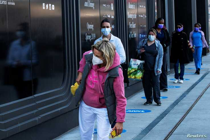 Health workers wait in line to get food near the Jacob K. Javits Convention Center, as the outbreak of the coronavirus disease …