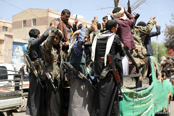 Armed Houthi followers ride on the back of a truck outside a hospital in Sanaa, Yemen April 8, 2020. Picture taken April 8,…