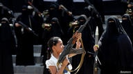 A girl holds a rifle in front of women loyal to the Houthi movement, who are taking part in a parade to show support for the movement in Sana'a, Yemen.