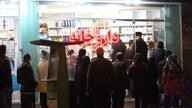 A line of customers in front of a pharmacy in Iran