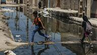Children in Ahvaz, Iranian southern city, are walking though sewage