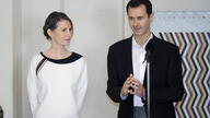 Syria's President Bashar al-Assad stands next to his wife Asma, as he addresses injured soldiers and their mothers during a…