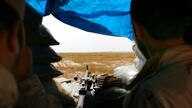 FILE - In this Monday, April 20, 2015 file photo, two Sunni fighters overlook an Islamic State group-held village on the other…
