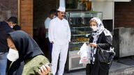 Iranians pass by a restaurant in the capital city of Tehran, on May 26, 2020. - Iran on May 25, reopened major Shiite shrines…