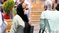 A pedestrian wearing a protective mask due to the COVID-19 coronavirus, walks along a street in the Iranian capital Tehran on…