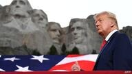 US President Donald Trump gestures as he arrives for the Independence Day events at Mount Rushmore National Memorial in…