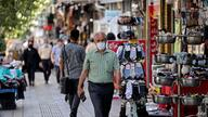 Iranians wear face masks as a measure against the Covid-19 coronavirus, in a street in the capital Tehran, on July 7, 2021. …