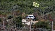A Hezbollah flag flutters on the Lebanese side of the border fence with Israel, near the northern Israeli settlement of Shtula…