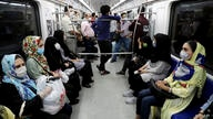 People wearing protective face masks to help prevent the spread of the coronavirus sit inside a train in Tehran, Iran,…