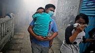 People move away as health workers fumigate a slum to prevent an outbreak of dengue fever in Jakarta, Indonesia, on Monday,…