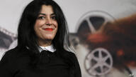 """Director, illustrator and author Marjane Satrapi poses for photographers as she arrives to present the movie """"La Bande des…"""