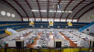 COVID-19 patients lie on beds in a field hospital built inside a gym in Santo Andre, on the outskirts of Sao Paulo, Brazil,…