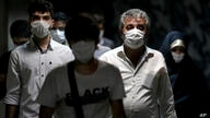 People wearing protective face masks to help prevent the spread of the coronavirus walk in a metro station, in Tehran, Iran,…
