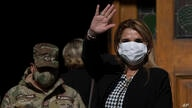 Bolivia's interim President Jeanine Anez, wearing a face mask to help curb the spread of the new coronavirus, waves during a…