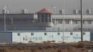 FILE - In this Monday, Dec. 3, 2018, file photo, a guard tower and barbed wire fences are seen around a facility in the Kunshan…