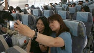 Participants take selfies in the cabin during a mock trip abroad at Taipei Songshan Airport in Taipei, Taiwan, Tuesday, July 7,…