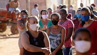 Wearing masks to curb the spread of the new coronavirus, locals line up to receive handouts of produce and basic supplies, in…