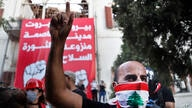 An anti-government protester shouts slogans after they enter the Lebanese Foreign Ministry building, seen in the background,…