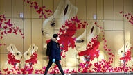 A young man wears a mask as he passes a easter advertising board downtown in Munich, Germany, Monday, March 30, 2020. In order…