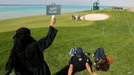 "A Saudi woman wearing Islamic ""Niqab"" raises ""quiet please"" sign as British Ashley Chesters plays out of a bunker at the 16th…"