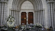 Flowers, messages and candles lie in front of the Notre Dame church, in Nice, France, Friday, Oct. 30, 2020. A new suspect is…