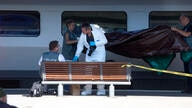 Members of the police forensics team take part in an investigation next to a Thalys train on the platform at Arras train…