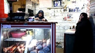 In this Tuesday, March 11, 2014 photo, butcher Zahra Shokouhi, left, tallies a bill for a customer at her shop in downtown…