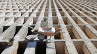 A cemetery worker prepares new graves at the Behesht-e-Zahra cemetery on the outskirts of the Iranian capital, Tehran, Iran,…