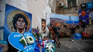Men hang on a wall a giant photo of the Gulf of Naples with soccer legend Diego Maradona topping the Vesuvius volcano, at the…