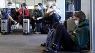 FILE- In this Oct. 15, 2020, file photo, passenger Cari Driggs, right, from Provo, Utah, waits to board a United Airlines…