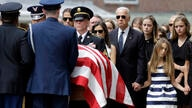 FILE - In this June 6, 2015, file photo, then-Vice President Joe Biden watches an honor guard carry a casket containing the…