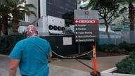 A medical worker walks past a refrigerated trailer parked outside the Cedars-Sinai Medical Center in Los Angeles Thursday, Jan…