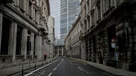 A person walks with an umbrella in light rain in the City of London financial district in London, Jan. 5, 2021, on the first…
