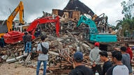 Rescuers search for survivors at the ruin of a local government building collapsed during an earthquake in Mamuju, West…