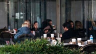 People sit on a coffee shop reopened for business as cafes, restaurants and other eateries reopened in some provinces across…