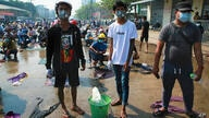 Anti-coup protesters prepare water and wet cloths to help extinguish tear gas canisters during a demonstration in Yangon,…