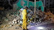 A man observes a destroyed building at the scene of a blast at a popular restaurant in the capital Mogadishu, Somalia Friday,…