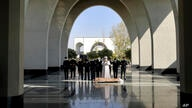 Mourners pray over the body of a person who died from COVID-19, at the Behesht-e-Zahra cemetery on the outskirts of the Iranian…