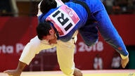 Uzbekistan's Bekmurod Oltiboev, in white, competes against Iran's Javad Mahjoub during their men's +100 kg judo bronze medal…