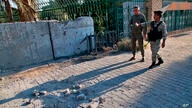 Security forces inspect the scene of the rocket attack at the gate of al-Zawra public park in Baghdad, Iraq, Wednesday, Nov. 18…