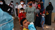 A health worker takes a mouth swab sample of a man to test for COVID-19 as others wait their turn to get tested at a hospital…