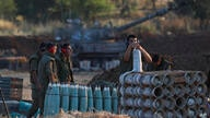Israeli soldier arms artillery shells next to an artillery unit at the Israeli Gaza border, Thursday, May 13, 2021. (AP Photo…