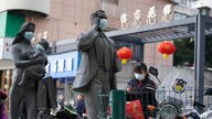 A woman wearing a mask walks past statues with masks placed on them in Wuhan in central China's Hubei province on Friday, Jan…