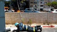 An Israeli firefighter takes cover as rocket fired from Gaza strip hit the southern Israeli city of Ashkelon, Tuesday, May 11,…