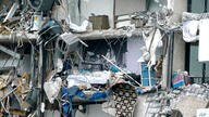 Household items and debris dangle from a partially collapsed multistory beachfront condo, Thursday, June 24, 2021, in Surfside,…