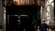 Police officers stand in front of the 'Grand Hotel Vienna' where where closed-door nuclear talks take place in Vienna, Austria,…