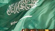 FILE - In this March 22, 2018, file photo, an honor guard member is covered by the flag of Saudi Arabia in Washington. Saudi…