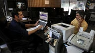 In this Thursday, July 25, 2019 photo, an internet cafe manager works on his computer as a man talks on his cell phone in…