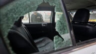 A police officer examines a damaged car at the site of a firing incident, in Karachi, Pakistan, Wednesday, July 28, 2021…